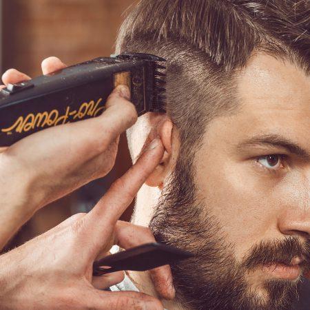 Un homme brun se fait faire une coupe à la tondeuse